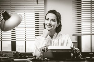 35506381 - 1950s style secretary working at office desk and smiling with hand on chin